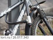 Купить «Велосипед, пристегнутый замком в металлической стойке», фото № 26017343, снято 14 апреля 2017 г. (c) Сергей Спритнюк / Фотобанк Лори