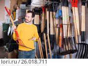 Купить «Smiling man choosing new pitchfork», фото № 26018711, снято 2 марта 2017 г. (c) Яков Филимонов / Фотобанк Лори