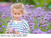 Little adorable girl smelling colorful flowers outdoors. Стоковое фото, фотограф Дмитрий Травников / Фотобанк Лори