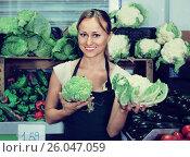Купить «Portrait of woman working in fruit shop showing fresh cabbage», фото № 26047059, снято 19 июня 2019 г. (c) Яков Филимонов / Фотобанк Лори