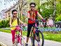 Bicycle path with children. Girls wearing helmet with rucksack ., фото № 26058383, снято 9 апреля 2016 г. (c) Gennadiy Poznyakov / Фотобанк Лори