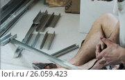 The worker cuts the metal profile. Стоковое видео, видеограф Кузьмов Пётр / Фотобанк Лори