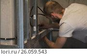 Купить «The worker drills the wall and fastens the frame», видеоролик № 26059543, снято 20 апреля 2017 г. (c) Кузьмов Пётр / Фотобанк Лори