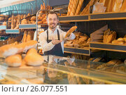Купить «Male shop assistant demonstrating delicious loaves of bread in bakery», фото № 26077551, снято 26 января 2017 г. (c) Яков Филимонов / Фотобанк Лори