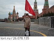 Купить «Мужчина держит красный флаг КПРФ на Красной площади в центре города Москвы во время возложения цветов к мавзолею В.И.Ленина в годовщину рождения вождя,  22 апреля 2017», фото № 26078135, снято 22 апреля 2017 г. (c) Николай Винокуров / Фотобанк Лори