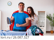 Купить «Super hero man husband ironing at home helping his wife», фото № 26087327, снято 5 января 2017 г. (c) Elnur / Фотобанк Лори