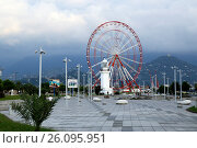 Cityscape of Batumi with Ferris wheel and old lighthouse at embankment over cloudy sky, Georgia (2016 год). Редакционное фото, фотограф Жукова Юлия / Фотобанк Лори