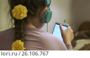 Купить «Girl with headphones listening to music from smartphone», видеоролик № 26106767, снято 26 апреля 2017 г. (c) Кузьмов Пётр / Фотобанк Лори