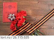 Купить «Орден Отечественной Войны лежит на военном билете на столе рядом с живыми красными гвоздиками, обёрнутыми в Георгиевскую ленту», фото № 26115035, снято 28 апреля 2017 г. (c) Максим Мицун / Фотобанк Лори