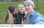 Three friends, do selfie for a walk in the park. Blonde, brunette and a young man. Have fun and enjoy life, видеоролик № 26116091, снято 28 апреля 2017 г. (c) Игорь Усачев / Фотобанк Лори