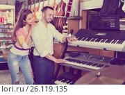 Купить «Young cheerful couple choosing synthesizer in shop», фото № 26119135, снято 19 августа 2018 г. (c) Яков Филимонов / Фотобанк Лори