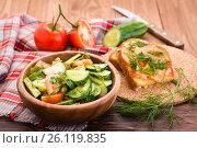 Салат из огурцов и помидоров в деревянной тарелке, запеченные бутерброды с сыром и овощи на столе. Стоковое фото, фотограф Елена Руй / Фотобанк Лори