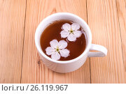 A cup of tea with flowers on a wooden background. Стоковое фото, фотограф Владимир Семенчук / Фотобанк Лори
