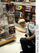 Купить «Покупатель берёт журнал с Президентом России Дмитрием Медведевым на обложке в книжном магазине Дубаи», фото № 26122707, снято 2 декабря 2008 г. (c) Free Wind / Фотобанк Лори