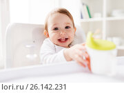 Купить «baby drinking from spout cup in highchair at home», фото № 26142231, снято 24 января 2017 г. (c) Syda Productions / Фотобанк Лори