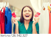 Купить «happy woman with sale tags on clothes at wardrobe», фото № 26142327, снято 19 февраля 2016 г. (c) Syda Productions / Фотобанк Лори