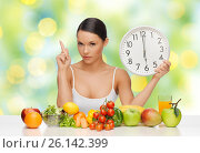 woman with food and big clock sitting at table. Стоковое фото, фотограф Syda Productions / Фотобанк Лори