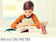 Купить «smiling, student boy reading book at home», фото № 26143155, снято 24 октября 2015 г. (c) Syda Productions / Фотобанк Лори