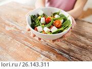 Купить «hands holding bowl of vegetable salad over table», фото № 26143311, снято 11 марта 2015 г. (c) Syda Productions / Фотобанк Лори