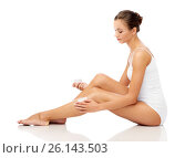 Купить «woman applying moisturizing cream to her leg», фото № 26143503, снято 9 апреля 2017 г. (c) Syda Productions / Фотобанк Лори