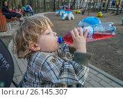 Купить «Мальчик пьет клюквенный морс из пластиковой бутылки», эксклюзивное фото № 26145307, снято 30 апреля 2017 г. (c) Виктор Тараканов / Фотобанк Лори