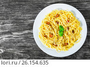 Купить «Spaghetti carbonara, basil, eggs yolk, grated parmesan cheese, bacon, close-up», фото № 26154635, снято 14 января 2016 г. (c) Oksana Zhupanova / Фотобанк Лори