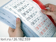 Купить «Hands of men hold the sheets of the calendar», фото № 26182559, снято 4 мая 2017 г. (c) Александр Калугин / Фотобанк Лори