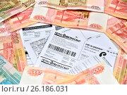 Купить «Счета на оплату коммунальных услуг в обрамлении бумажных купюр пять и одна тысяча рублей. Фокус на заголовке Петроэлектросбыт», фото № 26186031, снято 15 марта 2017 г. (c) Максим Мицун / Фотобанк Лори