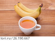 Cup of tea and bananas on a wooden background. Стоковое фото, фотограф Владимир Семенчук / Фотобанк Лори