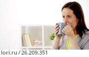 Купить «happy woman drinking tea or coffee at home», видеоролик № 26209351, снято 28 апреля 2017 г. (c) Syda Productions / Фотобанк Лори