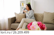 Купить «happy woman drinking tea or coffee at home», видеоролик № 26209499, снято 26 апреля 2017 г. (c) Syda Productions / Фотобанк Лори