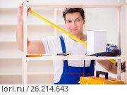 Купить «The worker man repairing assembling bookshelf», фото № 26214643, снято 13 февраля 2017 г. (c) Elnur / Фотобанк Лори