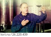 Купить «Worker of winery costs with glass of red wine near tanks», фото № 26220439, снято 12 октября 2016 г. (c) Яков Филимонов / Фотобанк Лори
