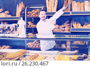 Купить «Male shop assistant demonstrating delicious loaves of bread in bakery», фото № 26230467, снято 26 января 2017 г. (c) Яков Филимонов / Фотобанк Лори