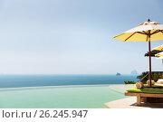 Купить «infinity pool with parasol and sun beds at ocean», фото № 26245947, снято 15 февраля 2015 г. (c) Syda Productions / Фотобанк Лори