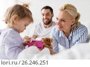 Купить «happy family with gift box in bed at home», фото № 26246251, снято 11 февраля 2017 г. (c) Syda Productions / Фотобанк Лори
