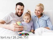 Купить «happy family with smartphone in bed at home», фото № 26246751, снято 11 февраля 2017 г. (c) Syda Productions / Фотобанк Лори