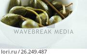 Купить «Green olives with stem in a bowl», видеоролик № 26249487, снято 19 февраля 2018 г. (c) Wavebreak Media / Фотобанк Лори