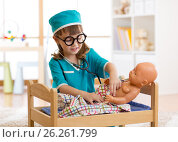 Купить «Adorable child with clothes of doctor plays with doll», фото № 26261799, снято 1 апреля 2017 г. (c) Оксана Кузьмина / Фотобанк Лори