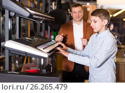 Купить «Father and teenage son examining keyboards in guitar shop», фото № 26265479, снято 29 марта 2017 г. (c) Яков Филимонов / Фотобанк Лори