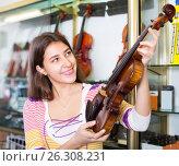 Купить «Girl choosing violin in music shop», фото № 26308231, снято 16 октября 2018 г. (c) Яков Филимонов / Фотобанк Лори