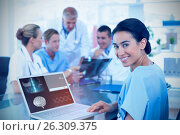 Купить «Composite image of beautiful smiling doctor typing on keyboard with her team behind», фото № 26309375, снято 18 октября 2018 г. (c) Wavebreak Media / Фотобанк Лори