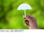 Купить «Composite image of hand holding an umbrella in paper», фото № 26309871, снято 23 апреля 2019 г. (c) Wavebreak Media / Фотобанк Лори