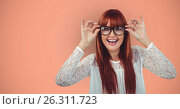 Купить «Cheerful redheaded female hipster wearing eyeglasses against orange background», фото № 26311723, снято 25 сентября 2018 г. (c) Wavebreak Media / Фотобанк Лори