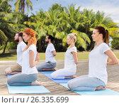 Купить «people making yoga in hero pose outdoors», фото № 26335699, снято 7 августа 2016 г. (c) Syda Productions / Фотобанк Лори