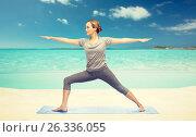 Купить «woman making yoga warrior pose on mat», фото № 26336055, снято 13 ноября 2015 г. (c) Syda Productions / Фотобанк Лори