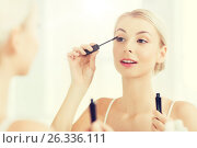 Купить «woman with mascara applying make up at bathroom», фото № 26336111, снято 13 февраля 2016 г. (c) Syda Productions / Фотобанк Лори
