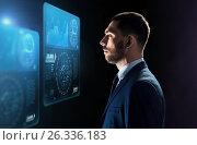 businessman looking at virtual screens over black, фото № 26336183, снято 9 марта 2017 г. (c) Syda Productions / Фотобанк Лори