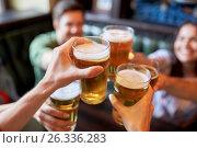 Купить «happy friends drinking beer at bar or pub», фото № 26336283, снято 14 июля 2016 г. (c) Syda Productions / Фотобанк Лори
