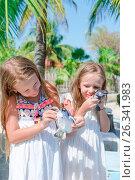Купить «Little kids with a small turtles in hands in the reserve. Girls love cute pets so much», фото № 26341983, снято 10 апреля 2017 г. (c) Дмитрий Травников / Фотобанк Лори